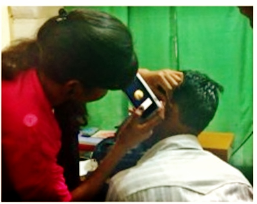 Community healthcare worker screening patients under ENT specialist supervision. Diagnoses and treatment plans made through the Shruti program are transmitted through the ClickMedix app and reviewed by specialists.